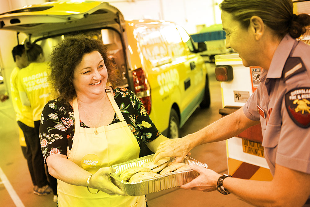Woman handing out food to firefighter
