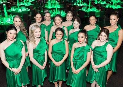 Group of ladies dressed in Emerald dresses with green tables behind them