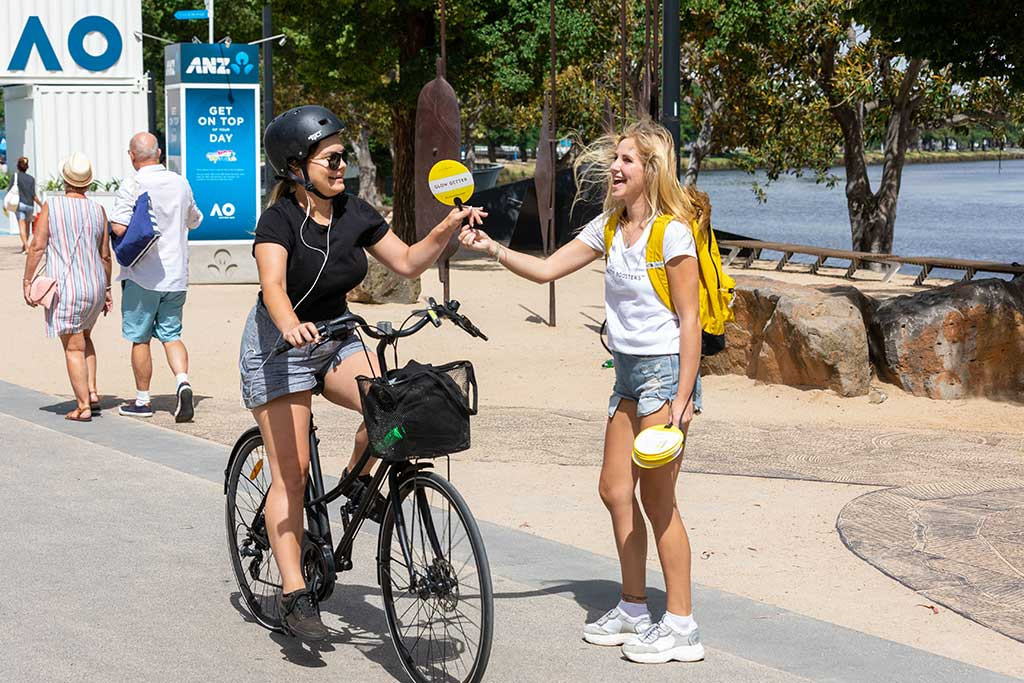 promo staff handing out merchandise to lady on bike - pr photography